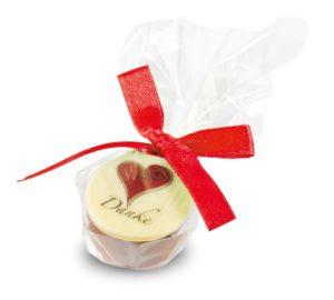 einer Praline mit Herz Motiv zum Muttertag oder Valentinstag. Kleines Geschenk für eine Freundin oder Freund. Mit einer roten Schleife